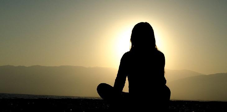 אישה יושבת ישיבה מזרחית בים מול השקיעה