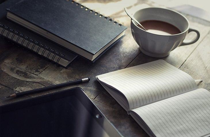 שולחן ועליו מונח יומן פתוח ולידו כוס קפה
