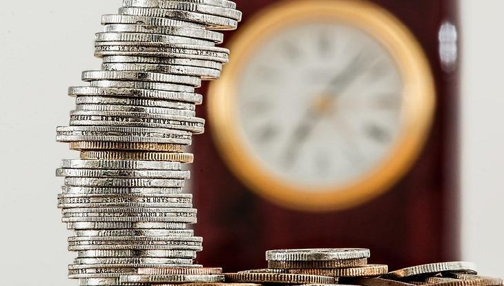ערמת מטבעות על רקע של שעון