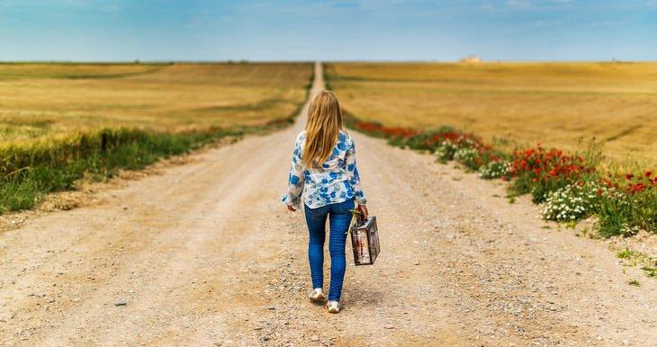 אישה עם מזוודה הולכת על שביל עפר