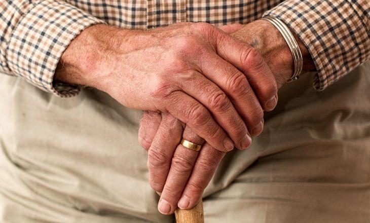 ידיים של קשיש שלובות ומחזיקות מקל הליכה