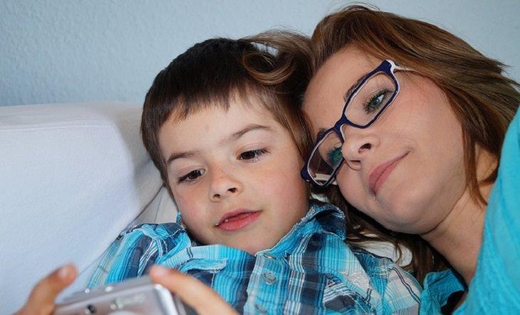 חינוך עדין לילדים: אם ובנה מביטים על תמונות במצלמה