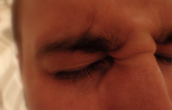 סימנים לשבץ: אדם מכווץ את עיניו בחוזקה