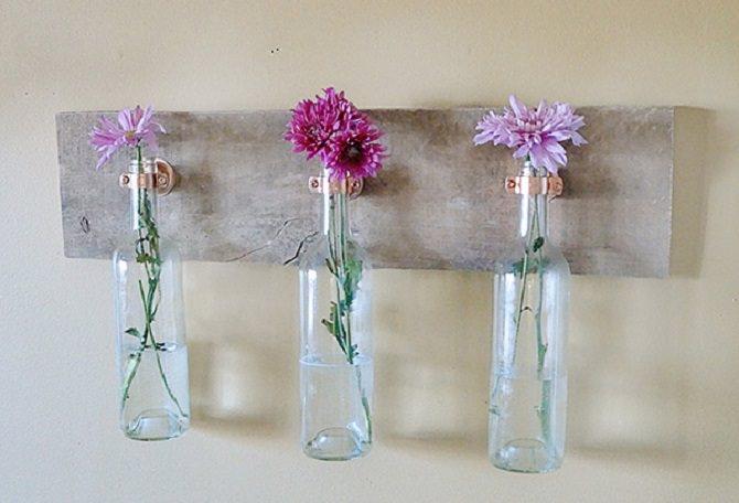 בקבוקי יין תלויים על קרש ובתוכם פרחים