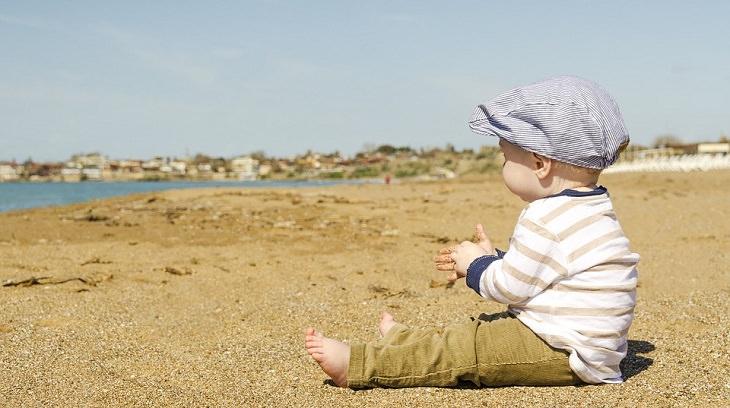 """""""מכתב לסבתא בגן עדן"""" מאת דוד אשל: ילד קטן חבוש קסקט יושב על חוף הים ומביט אל האופק"""