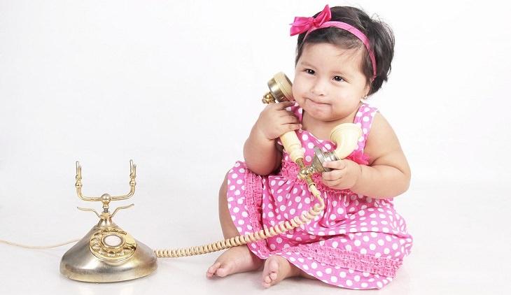 """""""מכתב לסבתא בגן עדן"""" מאת דוד אשל: ילדה קטנה לבושה בשמלת נקודות אוחזת שפורפרת של טלפון חוגה"""