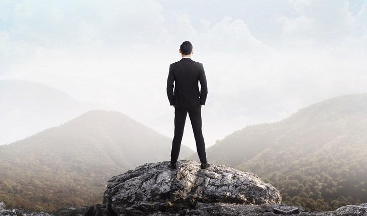 אדם עם חליפה על פסגת הר ומביט לאופק