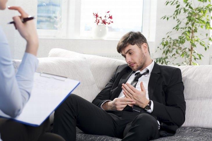 אדם מצוברח יושב על ספה