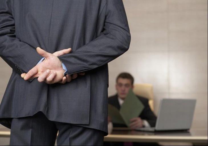 איש שעומד מול המעסיק שלו ומשלב את אצבעותיו מאחורי הגב