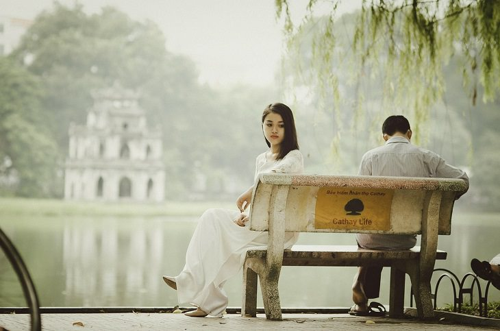 זוג יושב על ספסל עם הגב אחד לשני