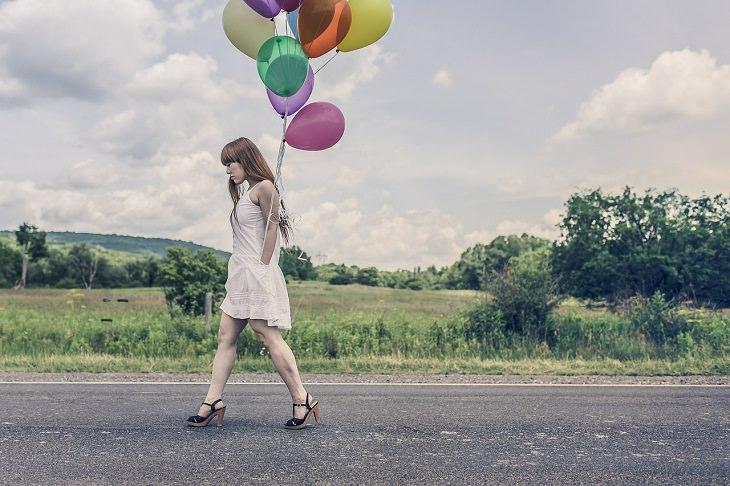 אישה הולכת עם אסופת בלונים
