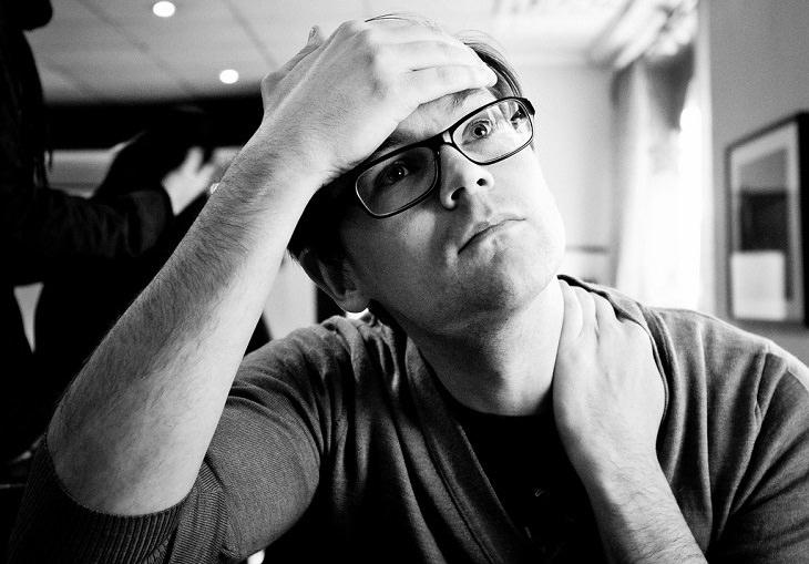 שמנים טבעיים לטיפול בכאבים: גבר עם משקפיים שסובל מכאב ראש