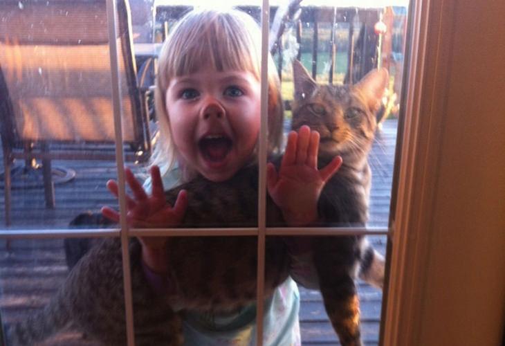 ילדה מחוץ לביתה מחזיקה חתול