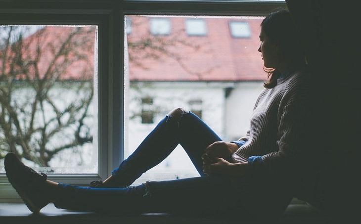 אישה יושבת על דופן החלון ומשקיפה החוצה