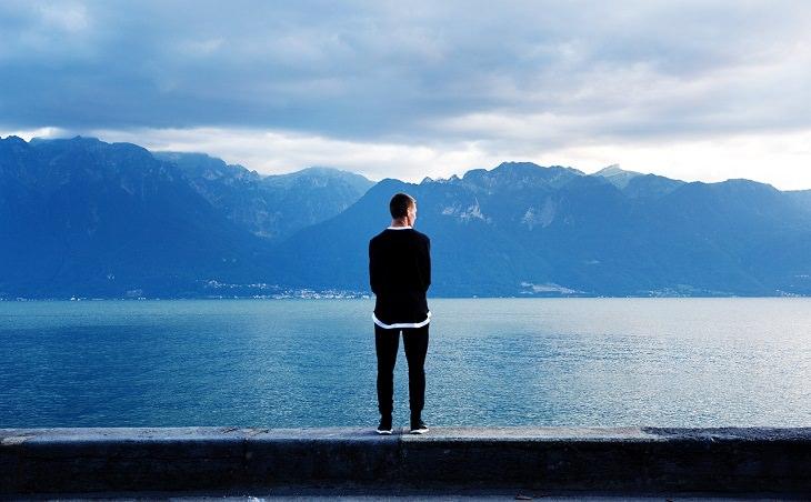 איש צופה אל נוף שנשקף מאגם
