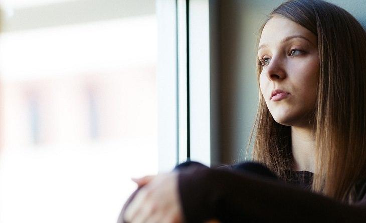 אישה עם מבד מוטרד בוהה מהחלון בביתה
