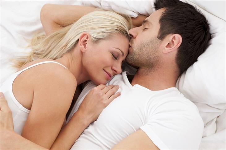 גבר מנשק אישה על המצח בזמן שהם שוכבים במיטה