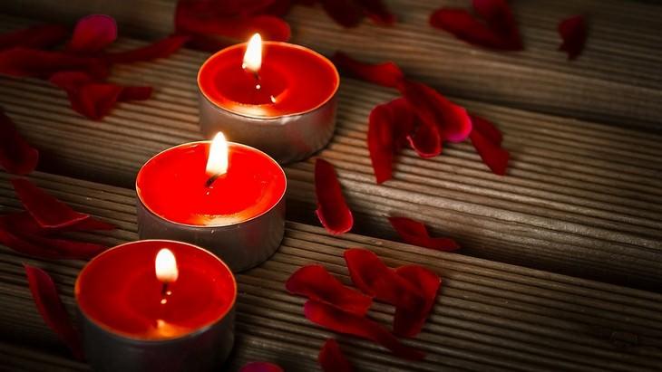 נרות אדומים דולקים על קרש עץ עם עלי כותרת אדומים לידם