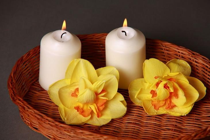 2 נרות בסלסילת קש עם שני פרחים צבעוניים