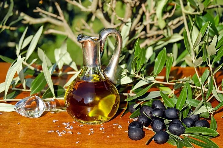 קנקן של שמן זכוכית עומד ליד עלי זית וזיתים שחורים