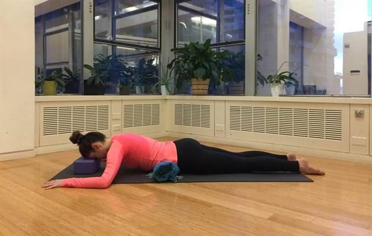 אישה שוכבת על הבטן כשתחתיה מגבות
