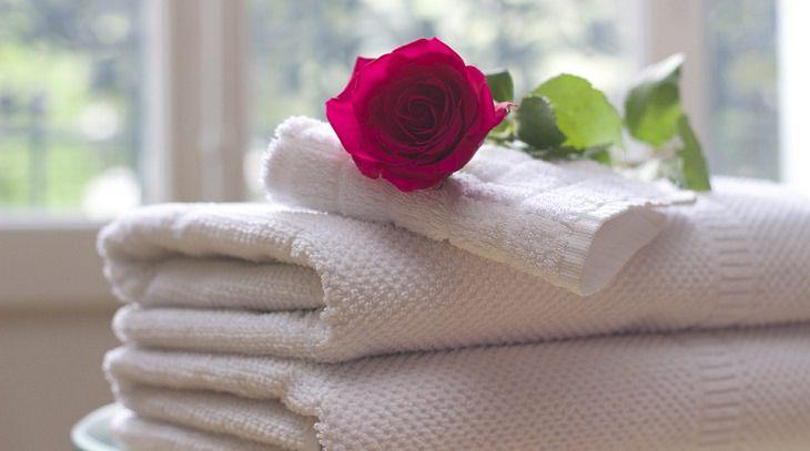 תרגיל פשוט לטיפול בצוואר תפוס: מגבות מקופלות ועליהן ורד