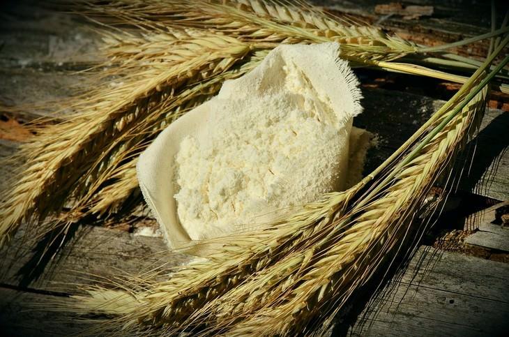קמח לבן בשק פתוח לצד שיבולי חיטה