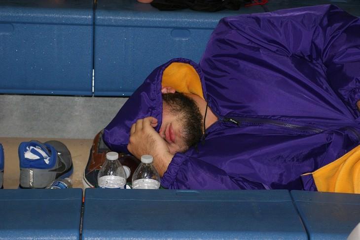 אדם ישן ומכסה את פניו בברדס סגול