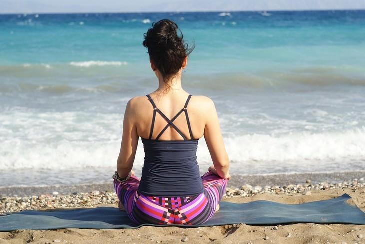 אישה יושבת על החוף