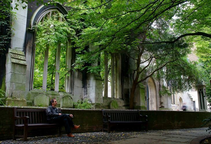 אדם יושב על ספסל בפארק וקיר בודד של כנסייה מאחוריו