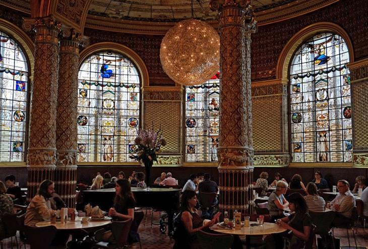 מסעדה מעוצבת עם חלונות ויטראז' ועמודים מעוטרים בפסלונים