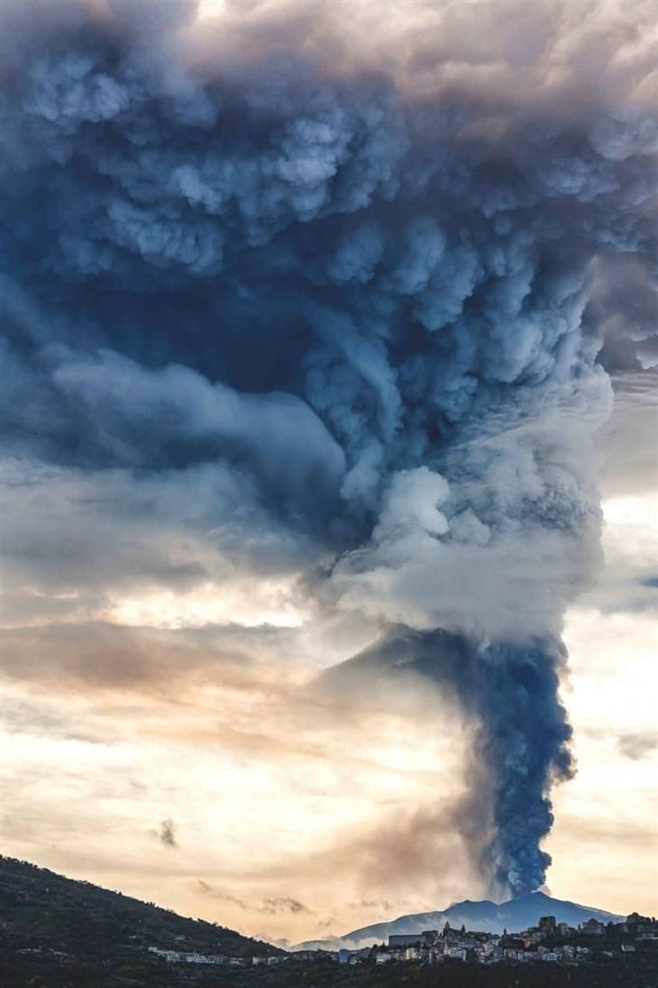 מחזה של עשן מיתמר מלוע הר געש כפי נראה מכפר קטן ומרוחק
