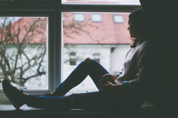 אישה יושבת לצד חלון ובוהה בנוף שמשתקף מבחוץ