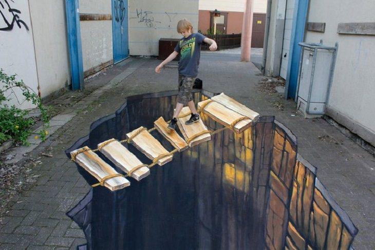 ילד צועד על ציור של תהום עמוקה עם גשר עץ רעוע