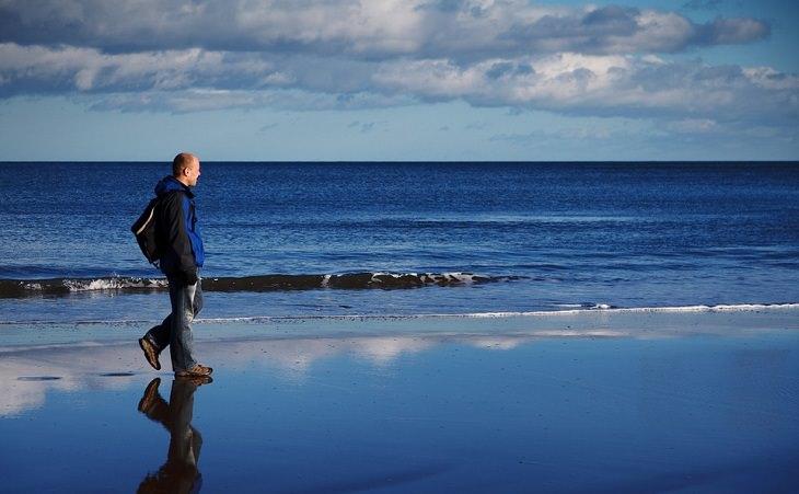אדם מבוגר צועד על החוף