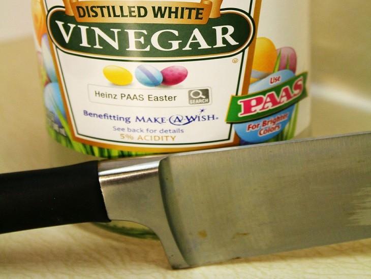 בקבוק חומץ ליד סכין חלודה