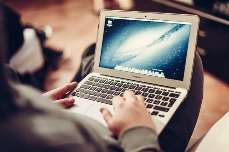 אדם עם מחשב נייד על החיק שלו