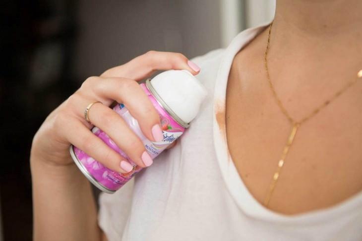 יד של אישה מחזקה מיכל של קצף גילוח ליד כתם על צווארון חולצה לבנה