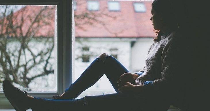 אישה יושבת על אדן החלון