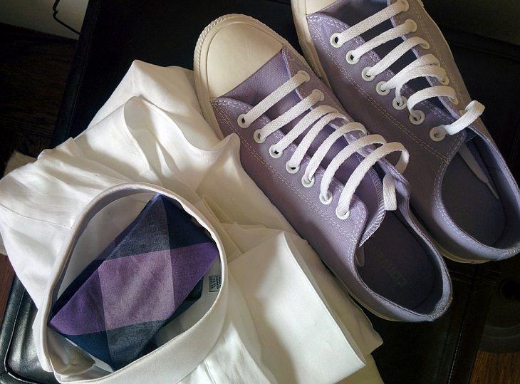 נעלי התעמלות סגולות מונחות ליד חולצה לבנה מקופלת