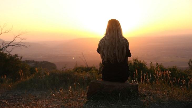 אישה יושבת על אבן בשקיעה עם גבה למצלמה
