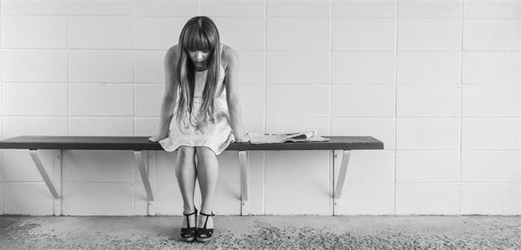 נערה יושבת על ספסל ונראית עצובה