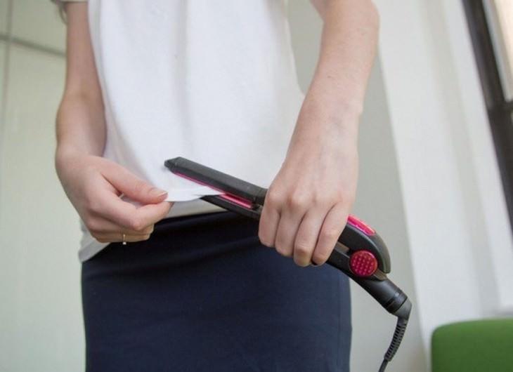 יד של אישה מחליקה קצה של חולצה בעזרת מחליק שיער