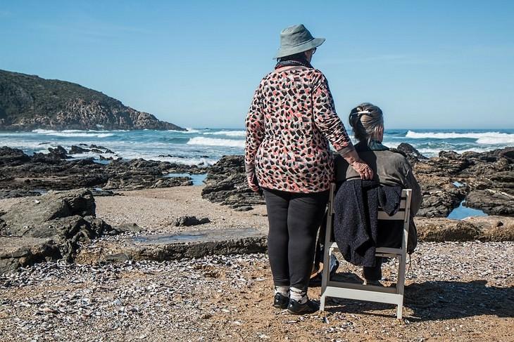 אישה עומדת ליד אישה מבוגרת על כיסא מול הים