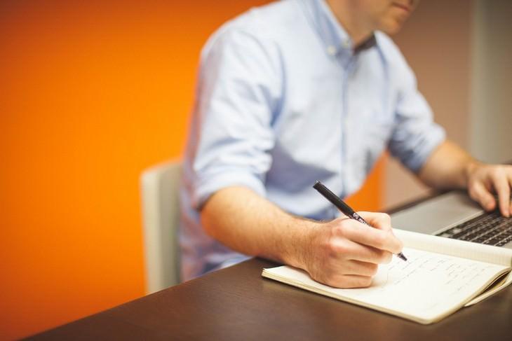 אדם יושב ליד מחשב נייד וכותב במחברת