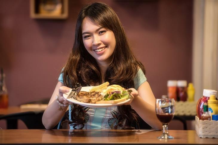 אישה מחזיקה צלחת עם אוכל