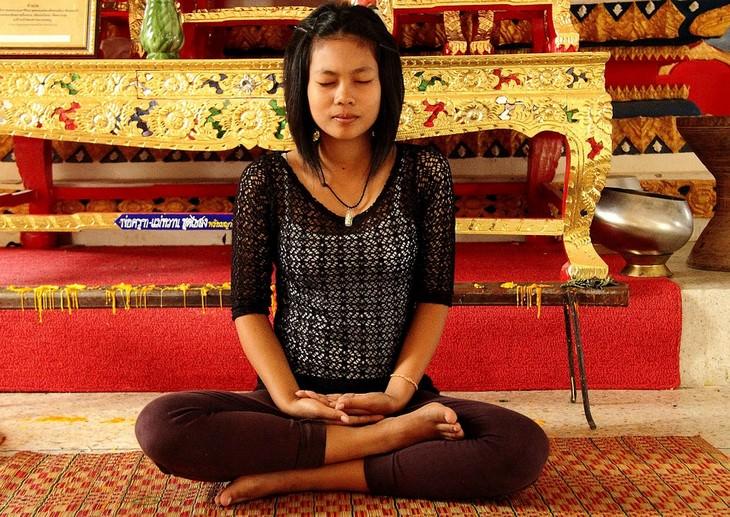 תרגילי נשימה לטיפול בגלי חום: אישה צעירה בתנוחת לוטוס