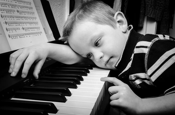 יתרונות לימוד נגינה לילדים: ילד משכיב את ראשו על פסנתר ולוחץ על אחד מכפתוריו