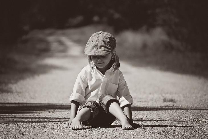 צילום באפור לבן של ילד יחף עם כובע יושב באמצע דרך לבד