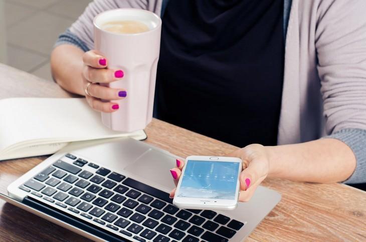 אישה יושבת ליד שולחן עבודה עם קפה ביד אחת, סמרטפון ביד השנייה ומחשב מולה